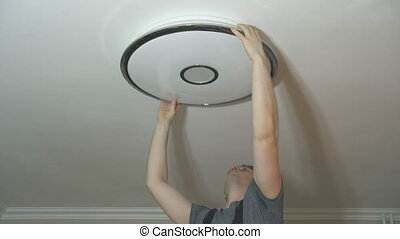 Male electrician mounting LED lamp at home.