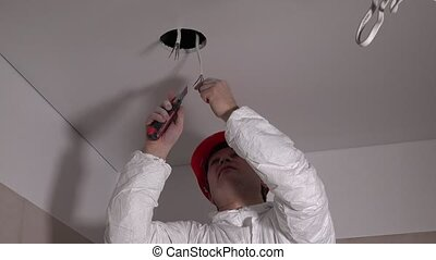 Male electrician repairing ceiling light