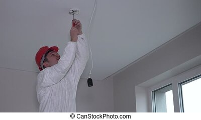 Male electrician worker mounting smoke detector fire alarm...