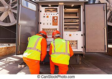 male electricians repairing transformer