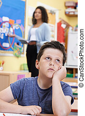 Male Elementary School Pupil Daydreaming In Class