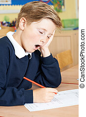 Male Elementary School Pupil Yawning In Classroom