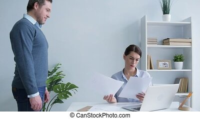 Male employee bringing business papers to his female boss