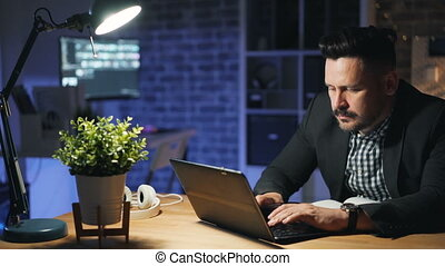 Male employee using laptop working overtime at night in...
