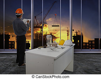 male engineer checking work flow in building construction site against beautiful dusky sky use for construction business and civil engineering