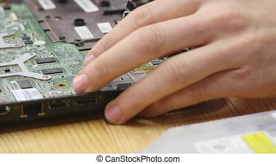 Male engineer computer repair works with disassembled laptop. One can see the computer's motherboard. Wooden table top view