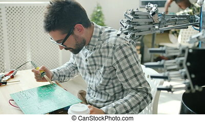 Male engineer is fixing robot microcircuit board with soldering iron in office using modern tool indoors. People, engineering and occupation concept.