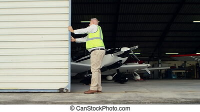 Male engineer opening shutter of hangar 4k - Male engineer...