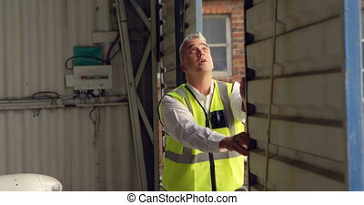 Male engineer opening shutter of aerospace hangar 4k