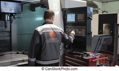 Male Engineer Operating CNC Machinery On Factory Floor....