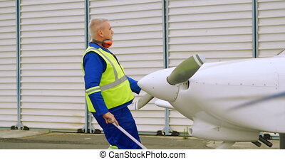 Male engineer pulling an aircraft 4k