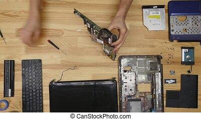 Male engineer repairs laptop. Wooden table top view.