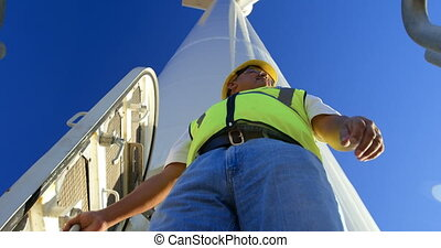 Male engineer standing on a wind mill in the wind farm 4k -...