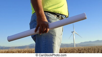 Male engineer standing with blueprint in the wind farm 4k -...