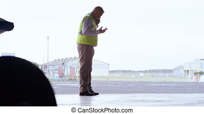 Male engineer talking on mobile phone in hangar 4k - Male...