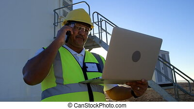 Male engineer talking on mobile phone while using laptop 4k...