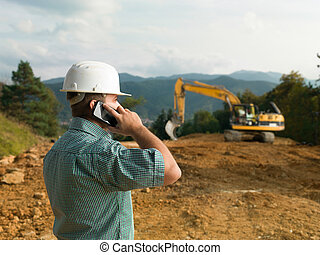 male engineer talking on the phone while supervising ...