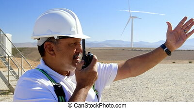 Male engineer talking on walkie-talkie in the wind farm 4k -...