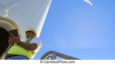 Male engineer using digital tablet near in the wind farm 4k...