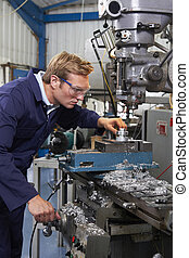 Male Engineer Using Drill In Factory