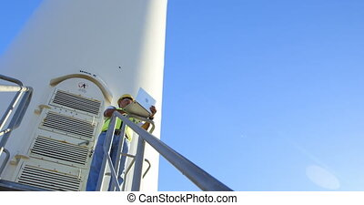 Male engineer using laptop in the wind farm 4k - Male...