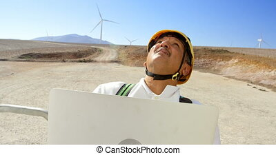Male engineer using laptop in the wind farm 4k - Male...