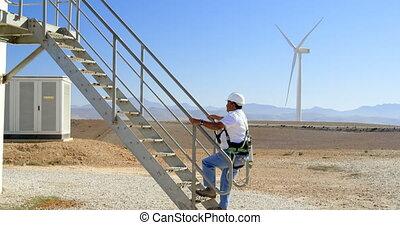 Male engineer walking upstairs in the wind farm 4k - Male...