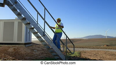 Male engineer walking upstairs in the wind farm 4k - Male...
