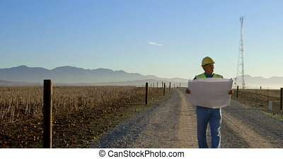Male engineer walking with blueprint in the wind farm 4k -...