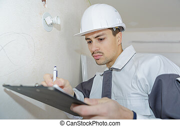 male engineer writing on clipboard at construction site