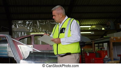 Male engineer writing on clipboard in hangar 4k - Male...
