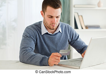 Male entering credit card information in his notebook -...