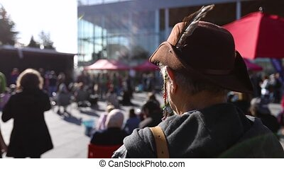 An elderly male activist in old fashioned mountaineers hat with selective focus is seen from the back listening to speeches at environmental rally