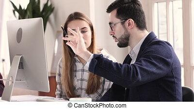 Male executive mentor training female intern learning ...