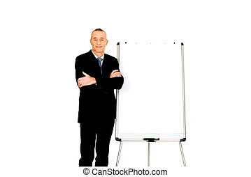 Male executive standing near flip chart