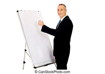 Male executive writing on a flipchart - Mature businessman...