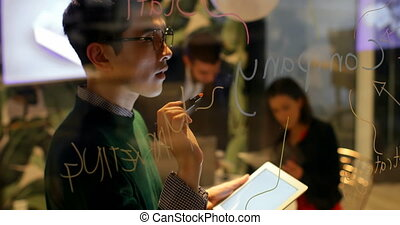 Male executive writing on glass board while using digital tablet in office 4k