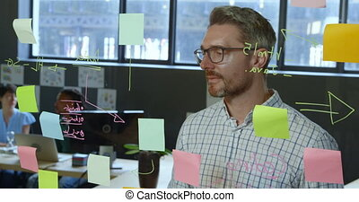 Male executive writing on glass wall in office 4k