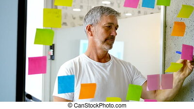 Male executive writing on sticky note on glass wall 4k -...