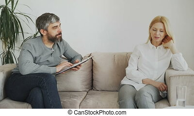 Male experienced psychologist talking and listening to upset female patient and writing notes on clipboard in his office