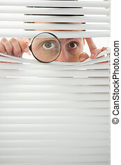 Male eyes spying through roller blind with magnifier - ...