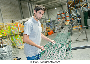 Male factory worker producing fencing