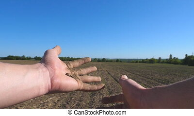 Male farmer hands holds a handful of dry ground and checks...