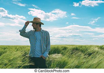 Male farmer walking through wheat field