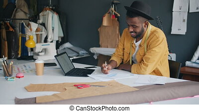 Male fashion designer drawing clothes using laptop creating...