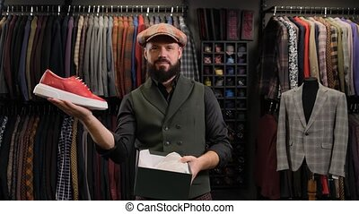 male fashion designer or salesperson taking a shoe out of a box and demonstrates it. Store for man