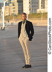 Male fashion model in trendy clothes standing outdoors