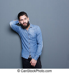Male fashion model posing on gray background