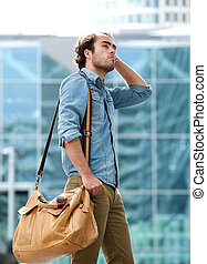 Male fashion model posing with leather bag