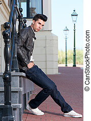 Male fashion model relaxing outdoors